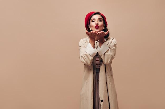 Очаровательная женщина в красном берете и дует поцелуй на бежевом фоне. стильная дама с темными волосами в длинном светлом пальто позирует на камеру.