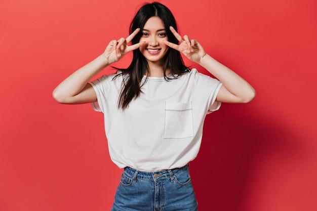 세련된 티셔츠에 매력적인 여성이 미소 짓고 평화 징후를 보여줍니다.
