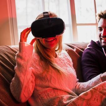 Charming woman in VR glasses near boyfriend