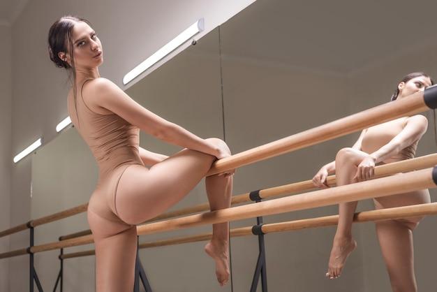 매력적인 여자는 거울 근처의 댄스 스튜디오에서 뻗어 있습니다. 춤, 발레의 개념입니다. 전문 장비. 혼합 매체