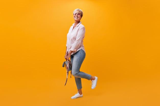 Affascinante donna in jeans, camicia e occhiali da sole pone su sfondo arancione