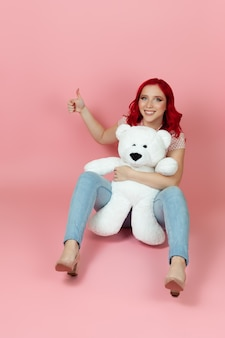 Charming woman in jeans with red hair holds a large white teddy bear and gives a thumbs up