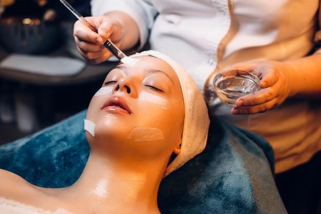Очаровательная женщина, опираясь на спа-кровать с закрытыми глазами, делает антивозрастную маску в оздоровительном спа-центре.