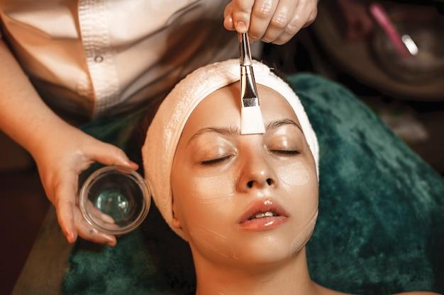 Очаровательная женщина, опираясь на спа-кровать с закрытыми глазами, пока косметолог наносит антивозрастную маску.