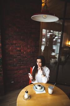 Очаровательная женщина смотрит на телефон в кафе. вкусный шоколадный торт и кофе на столе. яркое солнечное утро в кафе