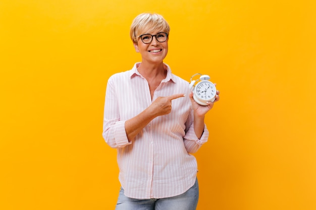 Charming woman in pink shirt pointing to alarm clock on orange background