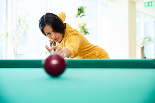 Очаровательная женщина играет в бильярд в помещении