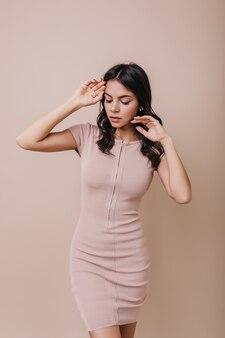 Очаровательная женщина позирует в облегающем платье. темноволосая модель смотрит вниз, нежно касаясь лица.