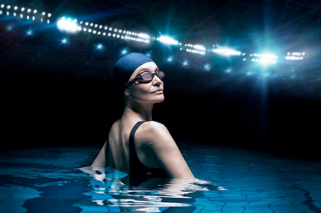 Charming woman posing in a pool against the backdrop of a stadium