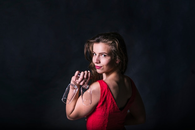 Charming woman posing while holding glasses
