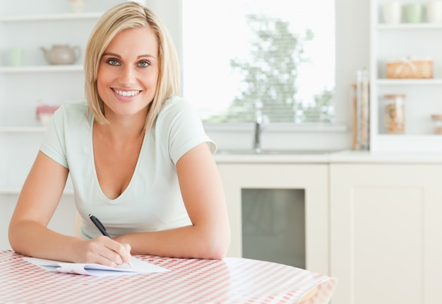 Charming woman proofreading a text looks into camera