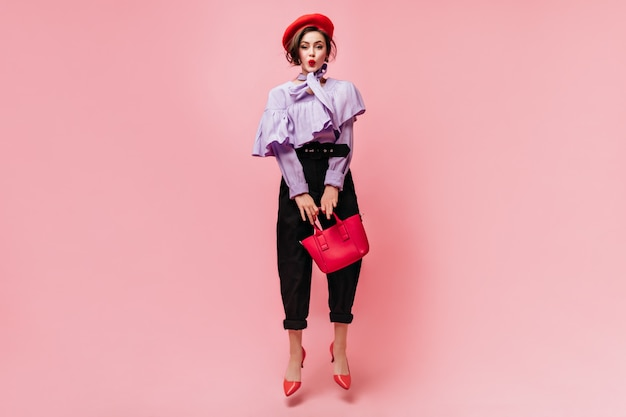 Charming woman in purple blouse and black pants whistles, holds red bag and jumps.