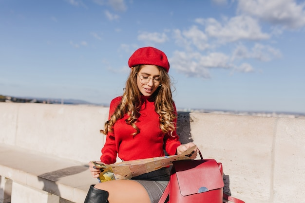 Charming woman in red knitted clothes looks closely at map