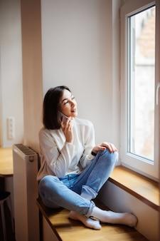 Donna affascinante nella sala che si siede vicino alla finestra in maglione bianco dell'abbigliamento casual