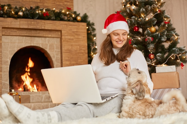 Charming woman sitting on floor with laptop, looks at her pet who sits near her, happy female wears red hat and casual sweater, lady with pekingese dog pose in festive christmas room near fireplace.