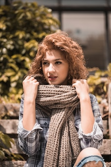 Charming woman sitting on steps and holding scarf