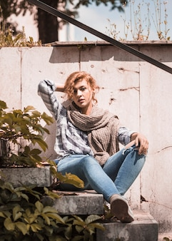 Charming woman sitting on steps and readjusting hairs
