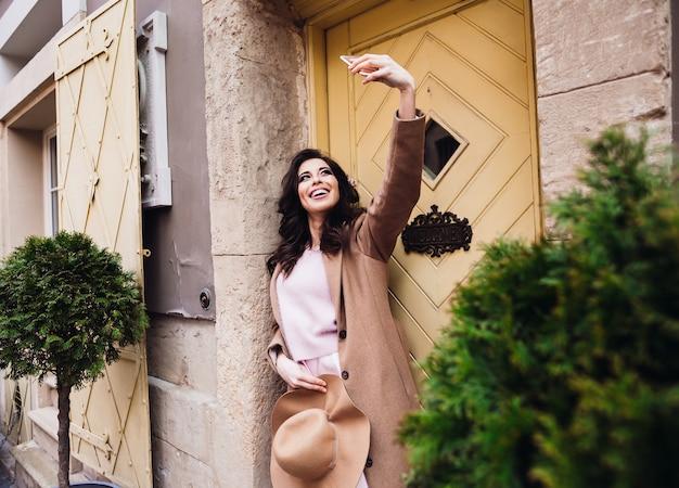 Affascinante donna sta davanti alla porta gialla e prende selfie sul suo iphone
