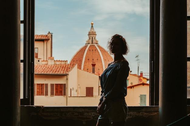 Очаровательная женщина стоит в палаццо веккьо на фоне базилики. концепция туризма и путешествий. смешанная техника