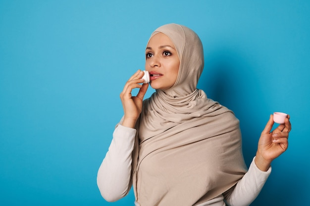 Charming woman in strict formal outfit and head scarf applying a lipstick, standing isolated