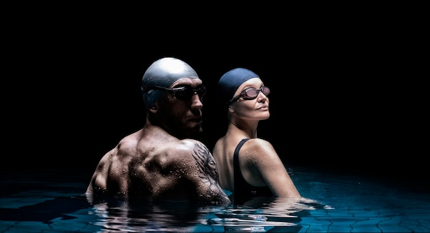 Charming woman and a strong man posing in the pool