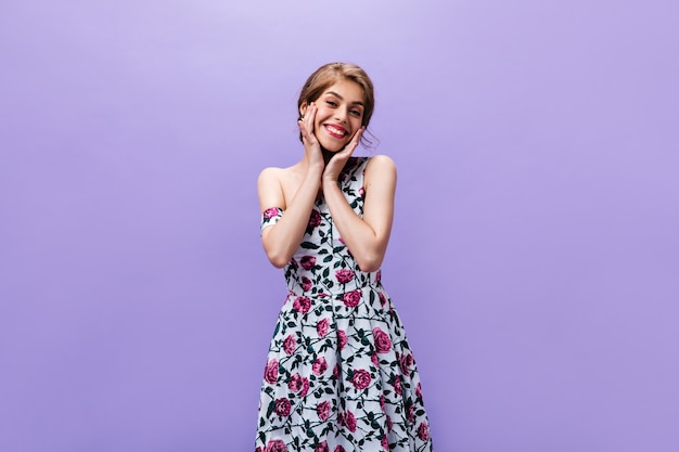 Charming woman in stylish dress poses on purple background. attractive cute girl in bright colorful clothes with smile looking into camera.
