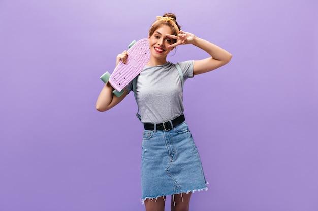 Affascinante donna in abito elegante posa con longboard e mostra il segno di pace. ragazza allegra in maglietta grigia e gonna di jeans con cintura sorridente.
