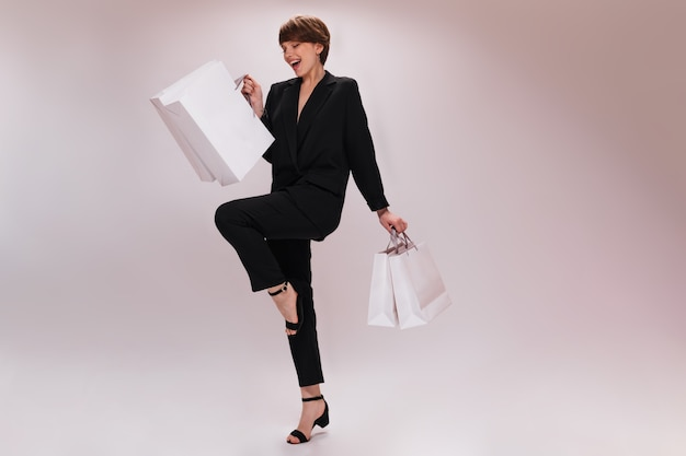 Charming woman in suit moves on isolated background and holds shopping bags. pretty lady in black jacket and pants jumps with white packages on white backdrop