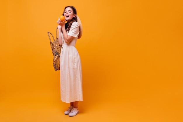 Affascinante donna in abito bianco estivo che tiene borsa stringa e arancia mordace.