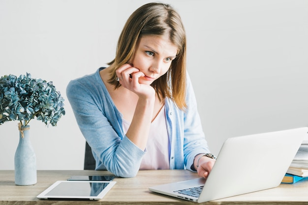 Charming woman thinking and using laptop
