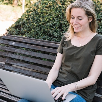Charming woman using laptop in park