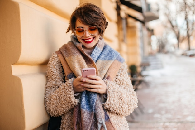 Charming woman using smartphone on street