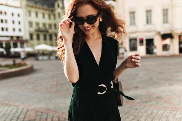 Affascinante donna in abito di velluto e occhiali da sole sorridente all'esterno