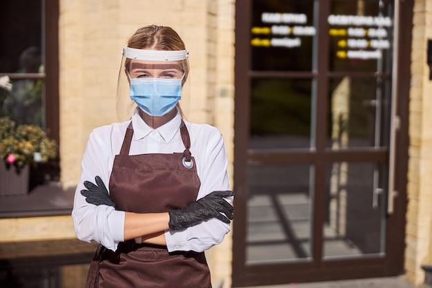레스토랑 근처의 여름 테라스에 서 있는 매력적인 여성 웨이터