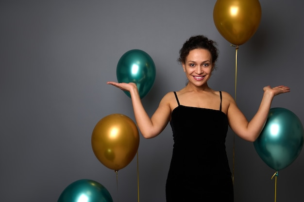 검은 벨벳 이브닝 드레스를 입은 매력적인 여성, 손바닥으로 카메라를 바라보는 미소, 광고를 위한 가상의 카피 공간을 보유하고 있습니다. 회색 배경에 생일, 크리스마스, 새해 개념