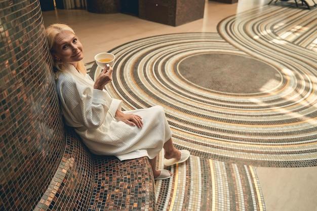 스파 센터에서 차 한잔에 앉아 흰색 부드러운 목욕 가운을 입고 매력적인 여자