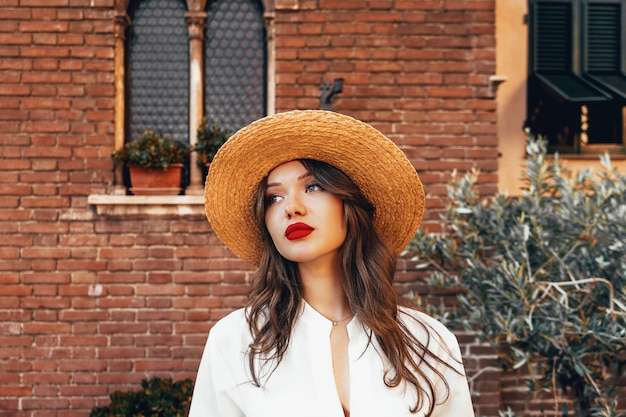 Charming woman in white blouse and straw hat. portrait of make up girl with long hair and big red lips. make up kit, summer vibe, concept of pure perfect skin. beauty vacation concept