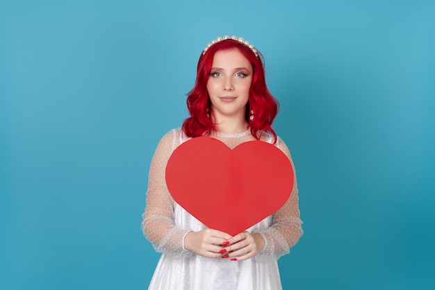 Charming  woman in white dress and with red hair holding big red paper heart