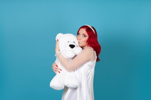 Charming woman in a white dress with red hair in profile kisses the cheek of a white teddy bear