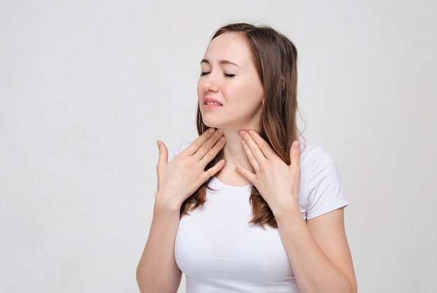 Charming woman in a white t-shirt  touches a throat that hurts a lot. anguine disease.