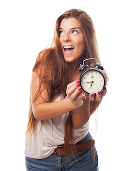 Charming woman with alarm clock in hands