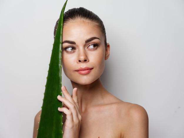 裸の肩を持つ魅力的な女性は肌の美容をきれいにします緑のアロエの葉