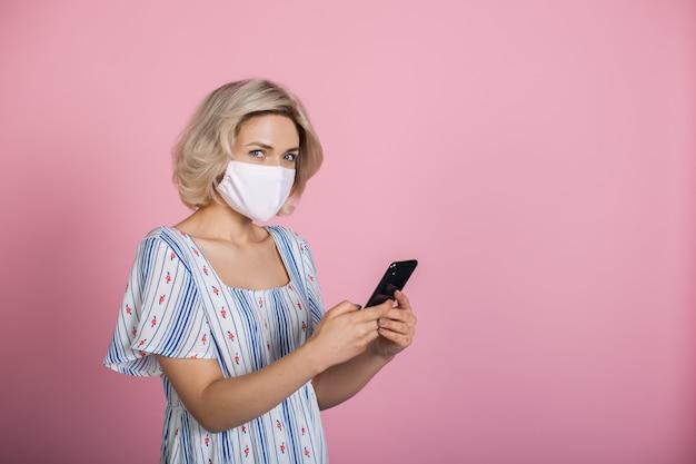 의료 마스크를 쓰고 금발 머리를 가진 매력적인 여자가 전화로 채팅하고 여유 공간이있는 분홍색 스튜디오 벽에 카메라를보고 있습니다.