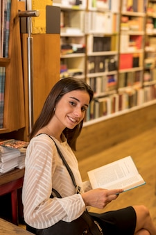 Charming woman with book looking at camera