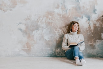 Charming woman with book near wall