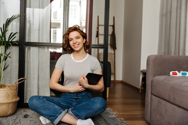 Charming woman with curly short hair holding computer tablet and sitting on floor in living room.