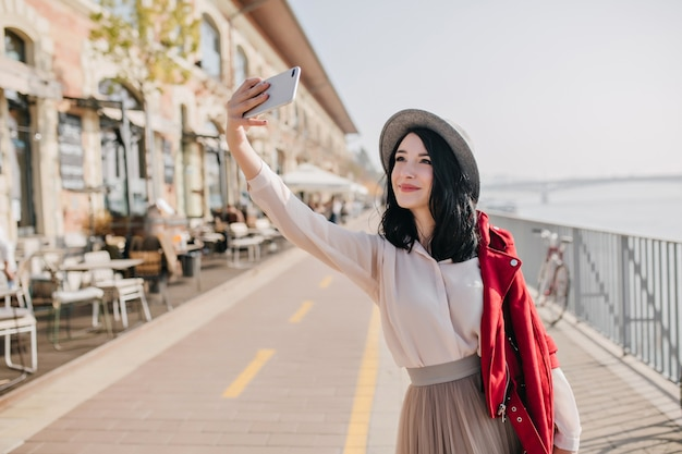 Charming woman with cute smile taking picture of herself in sunny day