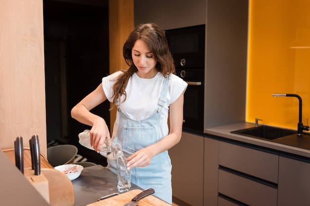 Charming woman with dark hair standing on bright kitchen and pouring fresh drinking water