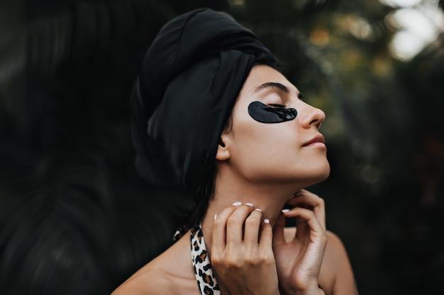 首に優しく触れる眼帯を持つ魅力的な女性。ターバンで洗練された白人女性の屋外ショット。