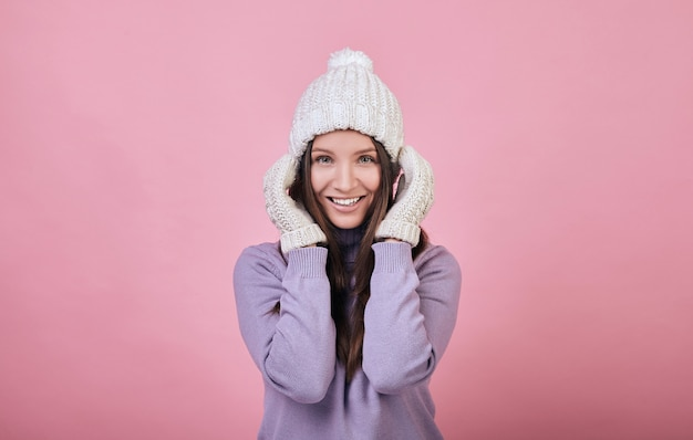 Charming woman with green eyes on a winter white knitted hat